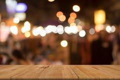 Det tomma träbrädet av den bruna tabellen av suddigt shoppar framme Royaltyfria Bilder
