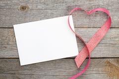 Det tomma valentinhälsningkortet och röd hjärta formade bandet Arkivfoto
