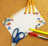Det tomma vita arket av papper för din text med blyertspennor, penna, scissor, gulnar highlighteren på korkbakgrunden Arkivbild
