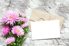 Det tomma vita hälsningkortet med den rosa aster blommar buketten och kuvertet Fotografering för Bildbyråer