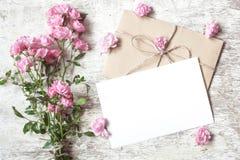 Det tomma vita hälsningkortet med rosa färgrosen blommar buketten Arkivbild