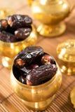Det torkade datumet bär frukt i guld- metallbunke. Royaltyfria Foton