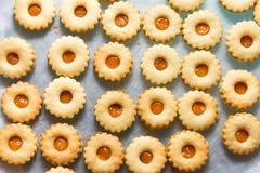 Det traditionella österrikiska hemmet bakade julkakaLinzer ögon med aprikosdriftstopp på bakplåten Process av förberedelsen cozy royaltyfria bilder