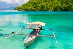 Det traditionella fartyget som svävar på de genomskinliga blåtten, tonade lagun av de avlägsna Togean eller Togian öarna, central Royaltyfri Bild