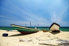 Det traditionella fiskarefartyget strandade på den öde sandiga stranden under ljus solig dag Royaltyfri Bild