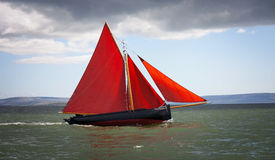 Det traditionella träfartyget med rött seglar Arkivbild