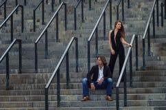 Det trendiga uppnosiga paret i eleganta dräkter står på ett grå färgG Arkivfoto