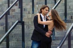 Det trendiga uppnosiga paret i eleganta dräkter står på ett grå färgG Arkivfoton