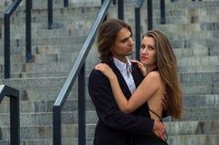 Det trendiga uppnosiga paret i eleganta dräkter står på ett grå färgG Arkivbild