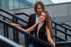 Det trendiga uppnosiga paret i eleganta dräkter står på ett grå färgG Royaltyfri Foto