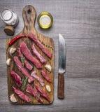 Det tunt skivade lammet med vitlök på en skärbräda med en kniv för kött, smör och saltar gränsen, textområde på trälantligt b Arkivfoton
