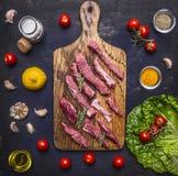 Det tunt skivade lammet med vitlök på en skärbräda med en kniv för kött, smör och saltar, grönsallat på trälantlig bakgrundsöverk Royaltyfria Foton