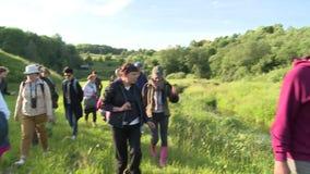 Det turist- folket går med handbokbotaniker framme Kunskap av naturen stock video