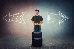 Det tvivelaktiga manhandelsresandeanseendet bak hans bagage måste välja hans nästa semesterdestination arkivbild