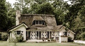 Det typiska franska bygdhuset med halmtäcker taket Arkivfoto
