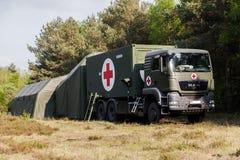 Det tyska räddningsaktionmittsystemet på lastbilar står i ett trä arkivbilder