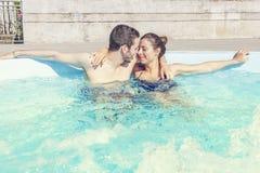Det unga älska paret kopplar av i hydromassagen Arkivfoton