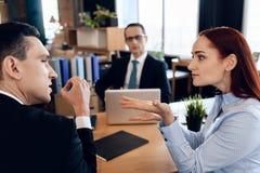 Det unga allvarliga paret konsulterar och att sitta i regeringsställning av skilsmässaförkämpe Det vuxna paret skilja sig från Royaltyfri Fotografi