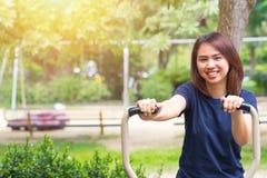 Det unga asiatiska leendet tycker om bröstkorgövning i parkera för sunt tonårigt royaltyfri foto