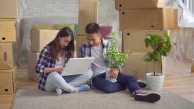 Det unga asiatiska paret kör in i en ny lägenhet som sitter på golvet och använder en bärbar dator arkivfilmer