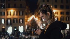 Det unga attraktiva kvinnaanseendet i stadsmitten på aftonen och använder smartphonen Folkmassa och ljus på bakgrunden stock video