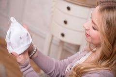 Det unga attraktiva kvinnainnehavet behandla som ett barn hatten, inre Royaltyfria Foton