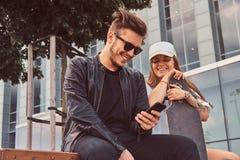 Det unga attraktiva paret sitter p? sommargatan arkivbild