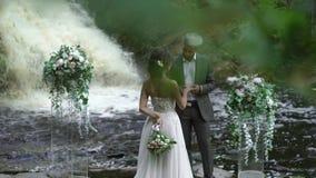 Det unga bröllopparutbytet ringer på ceremoni nära vattenfallet stock video