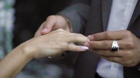 Det unga bröllopparutbytet ringer på ceremoni nära vattenfallet lager videofilmer