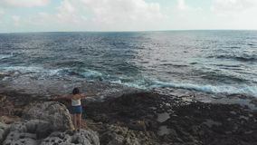 Det unga caucasian kvinnaanseendet på stort vaggar med det breda öppna seende stormiga havhavet för armar med vågor som slår kust arkivfilmer