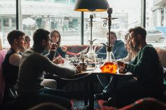 Det unga företaget har roligt och äter i stång röka en vattenpipa som meddelar i en orientalisk restaurang arkivbilder