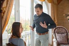 Det unga gifta paret grälar på fönstret arkivfoto