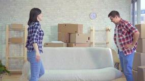 Det unga gifta paret tar bort vaxduken från soffan, når han har flyttat sig stock video