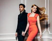 Det unga härliga modeparet flyttar sig snabbt Flickan fladdrar långt härligt rött hår Rym händer inomhus varm färg Fotografering för Bildbyråer