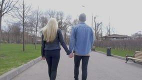 Det unga härliga paret går i parkera rymma för händer Dem beträffande komma för ` från kameran långsam rörelse stock video