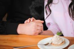 Det unga härliga paret rymmer varje - annat händer i ett kafé arkivfoto