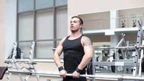Det unga hårda drevet för den starka mannen tränga sig in i idrottshall stock video