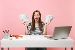 Det unga ilskna irriterade kvinnaskriet fördelade händer med packemassor av arbete för dollarkassapengar på kontoret på det vita  royaltyfria foton