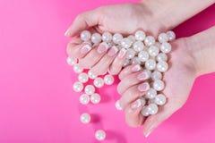 Det unga kvinnliga innehavet många pärlor i hand med fransman spikar polermedel som isoleras på rosa färger royaltyfri bild