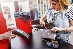Det unga kvinnliga kundanseendet på kassan som betalar med kreditkorten i kläder, shoppar royaltyfri foto
