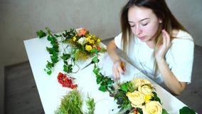 Det unga kvinnliga rekordet för blommaförlagehanterareuppehällen av blommor och skriver observation i anteckningsboksammanträde p stock video