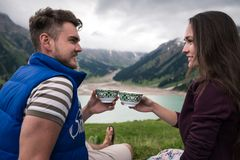 Det unga le paret ser de och rymmer i traditionella koppar för händer royaltyfri foto
