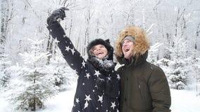 Det unga lyckliga paret är selfie som fotograferas i ett snöig begrepp för skogvinterlopp stock video
