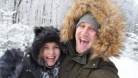 Det unga lyckliga paret är selfie som fotograferas i ett snöig begrepp för skogvinterlopp lager videofilmer
