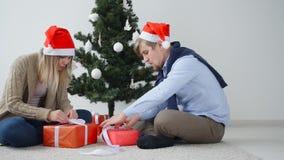 Det unga lyckliga paret öppnar julklappar i ett rum med en vit inre lager videofilmer