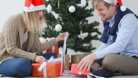 Det unga lyckliga paret öppnar julklappar i ett rum med en vit inre arkivfilmer