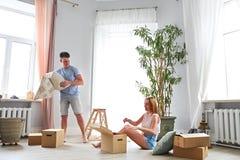 Det unga lyckliga paret i rum med flyttning boxas arkivfoton