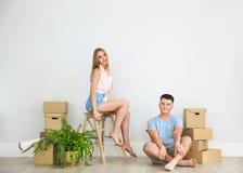 Det unga lyckliga paret i rum med flyttning boxas royaltyfri bild