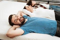 Det unga lyckliga paret med den gulliga pysen ligger på säng i madrasslager royaltyfri fotografi
