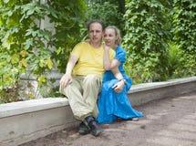 Det unga lyckliga paret sitter i berså tvinnade gräsplanerna Royaltyfri Bild